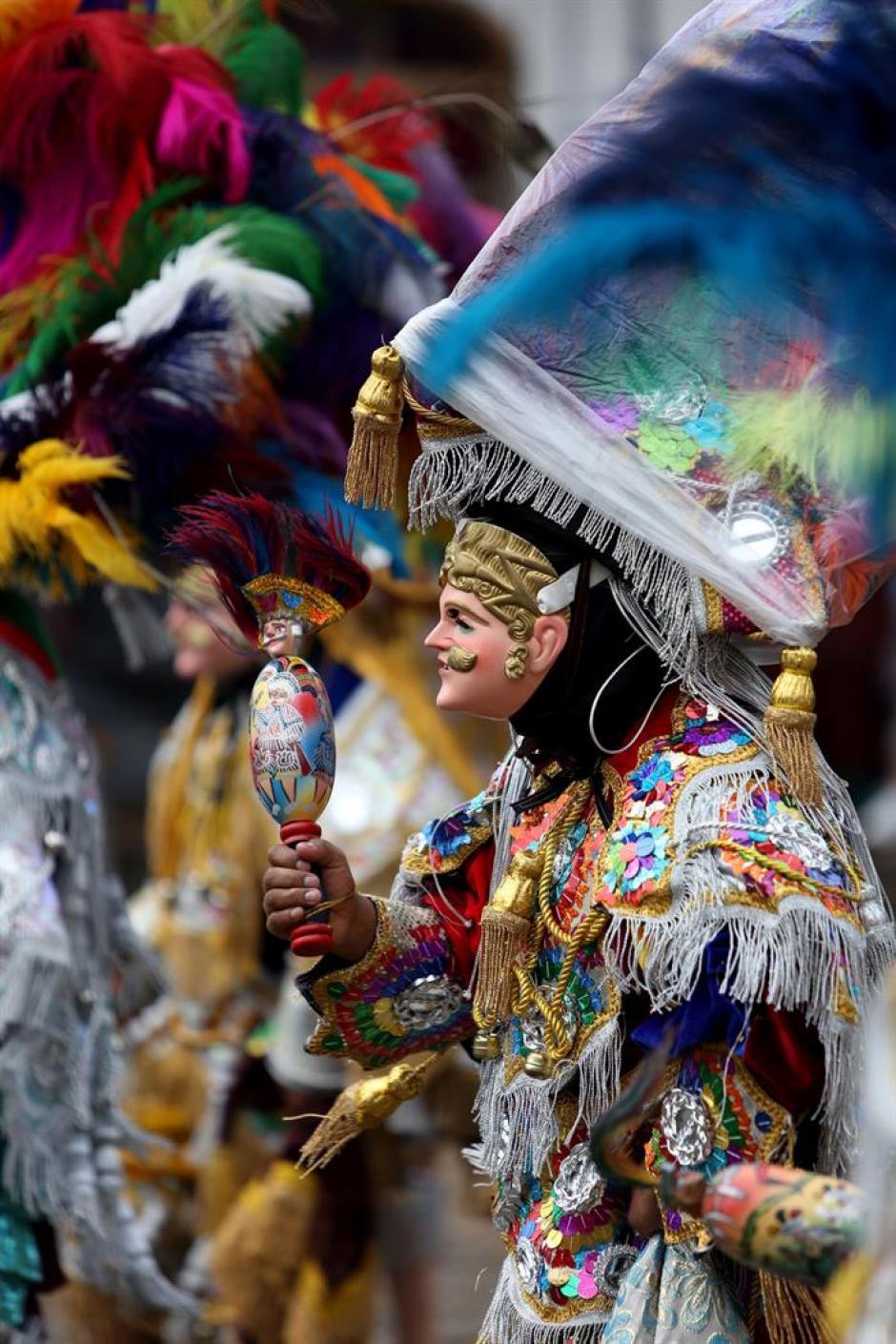 Un bailarín sostiene una elaborada miniatura de su traje, esto durante la celebración. (Foto: Esteban Biba/Soy502)