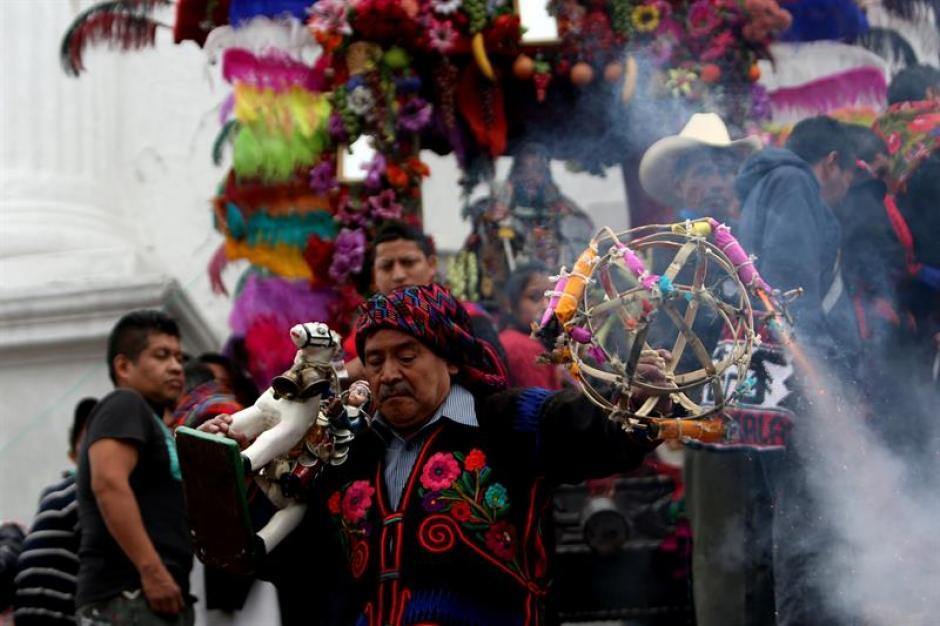 Un hombre baila mientras sostiene fuegos artificiales en el marco de la celebración de Santo Tomás, en Chichicastenango. (Foto: Esteban Biba/EFE)