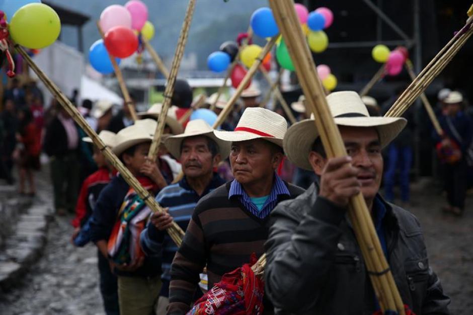 Con varas adornadas y globos, este grupo de fieles camina por las calles de Chichicastenango durante las celebraciones en honor a Santo Tomás. (Foto: Esteban Biba/EFE)