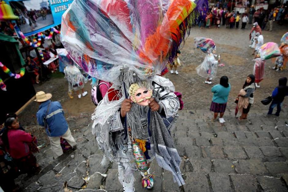 Un hombre sostiene su máscara tradicional mientras escala unas gradas en Chichicastenango. (Foto: Esteban Biba/EFE)