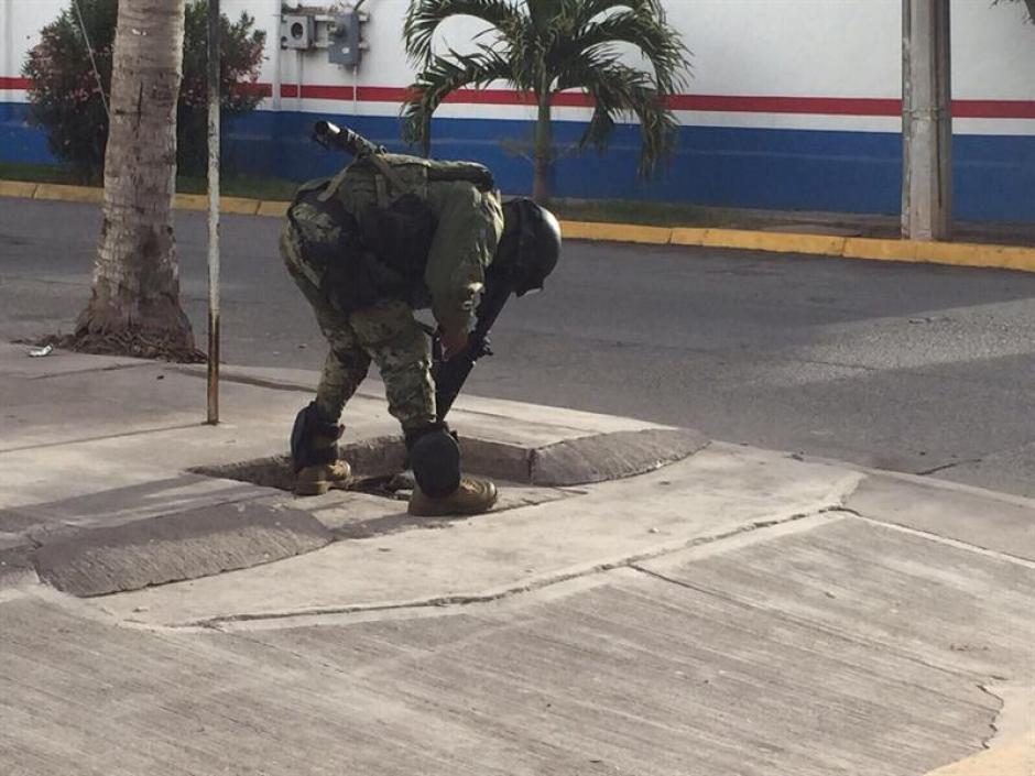 """Un integrante de la Marina Armada de México apunta con su arma hacia adentro de una alcantarilla en la ciudad de Los Mochis, estado de Sinaloa donde fue capturado """"El Chapo"""" Guzmán. (Foto: EFE)"""