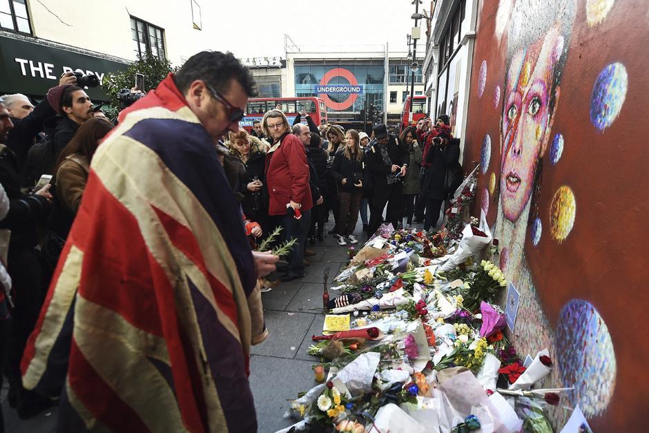 Fans del músico y cantante británico colocan flores y cartas frente a una pintura del rostro de Bowie (Foto: EFE/Andy Rain)