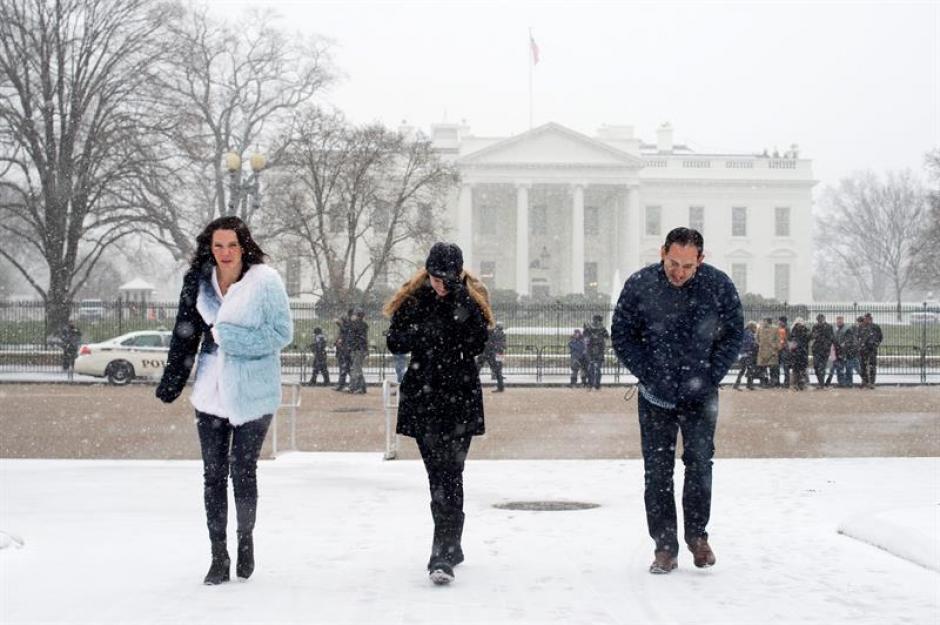 Varias personas caminan en medio de la tormenta junto a la Casa Blanca en Washington. (Foto: EFE)