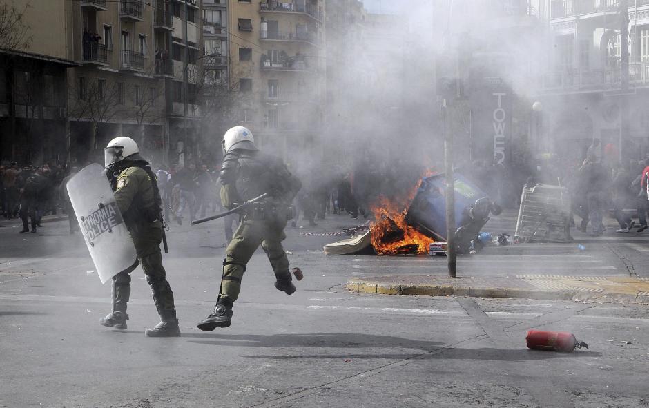 Varios policías antidisturbios tratan de esquivar un cóctel molotov lanzado por los manifestantes durante la protesta. (Foto: EFE)