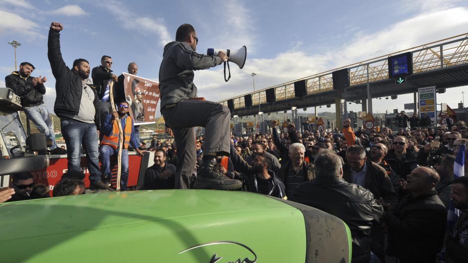 Un hombre con un megáfono lidera la marcha de un grupo de manifestantes en una protesta en Atenas. (Foto: EFE)