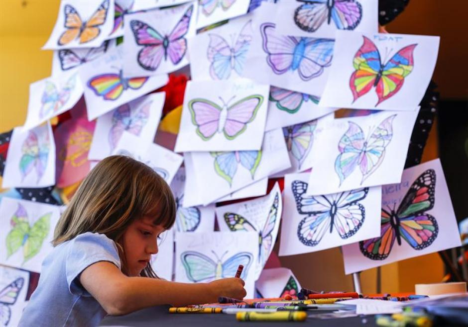 """Una niña pinta mariposas en la celebración del """"I Am Ali."""" (Foto: EFE)"""