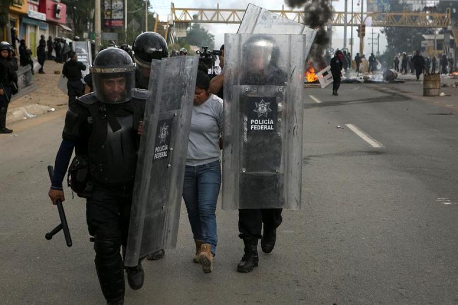Policías federales conducen a una detenida en la ciudad de Oaxaca durante los enfrentamientos. (Foto: Efe)