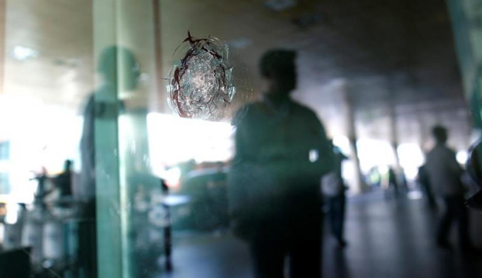 Varias personas caminan junto a cristales dañados tras un atentado en el aeropuerto internacional de Atatürk en Estambul, Turquía. (Foto: Efe)