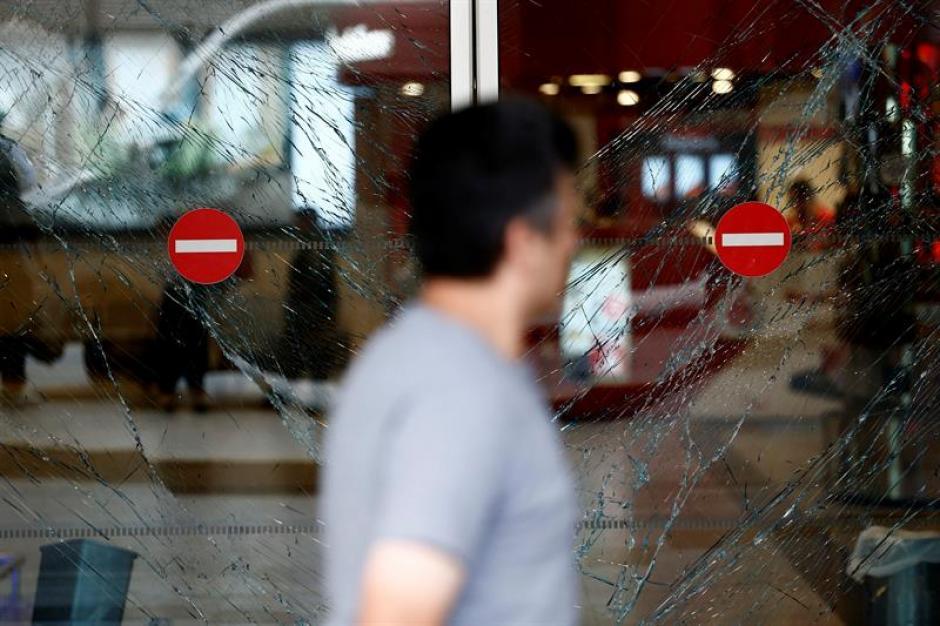 Un hombre camina junto a los cristales rotos de una puerta tras un atentado en el aeropuerto internacional de Atatürk en Estambul. (Foto: Efe)