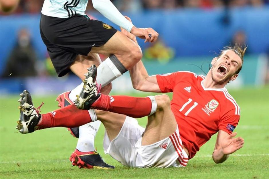 Gareth Bale recibe una fuerte entrada de un zaguero belga. (Foto: EFE)