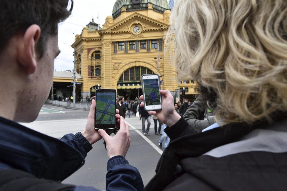 """Dos estudiantes prueban el nuevo juego """"Pokémon Go"""" en su móvil en Melbourne, Victoria, Australia. (Foto:  EFE/Julian Smith)"""
