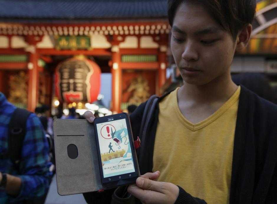 """Un joven japonés muestra en su móvil el juego """"Pokémon GO"""". (Foto: EFE/Kimimasa Mayama)"""