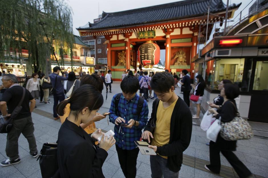 """Varios universitarios japoneses prueban en su móvil el juego """"Pokémon GO"""". (Foto: EFE/Kimimasa Mayama)"""