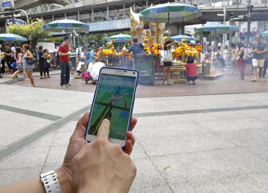 """Un turista juega al videojuego """"Pokemon Go"""" desde su teléfono móvil en el Santuario de Erawan en Bangkok, Tailandia. (Foto: EFE/Rungroj Yongrit)"""