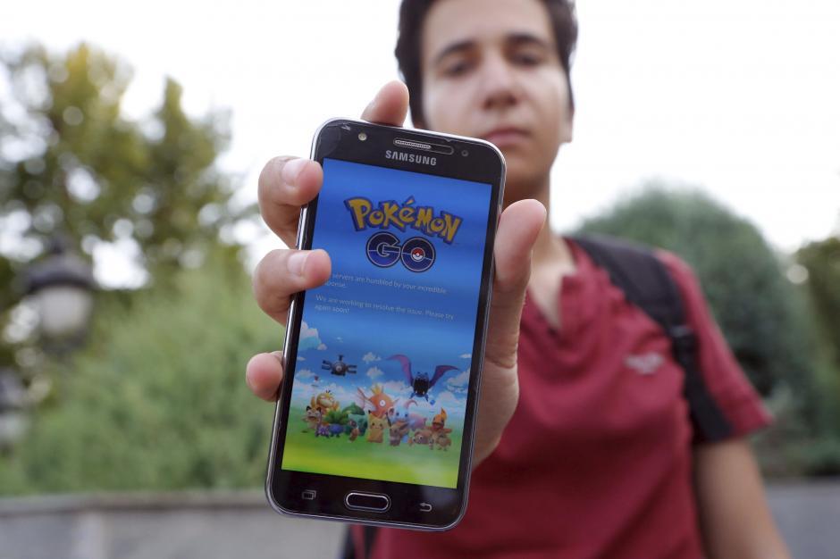 """Un adolescente muestra la pantalla de su teléfono móvil donde aparece el texto que dice que la aplicación de """"Pokémon GO"""" no puede conectarse en el parque Mellat de Teherán, Irán. (Foto: EFE/Abedin.Taherkenareh)"""