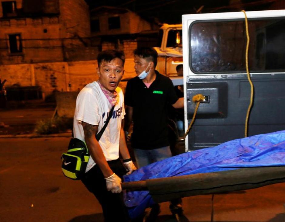 Un empleado de una funeraria transporta el cadáver de un presunto traficante de drogas tiroteado en una operación policial en Filipinas. (Foto: EFE)