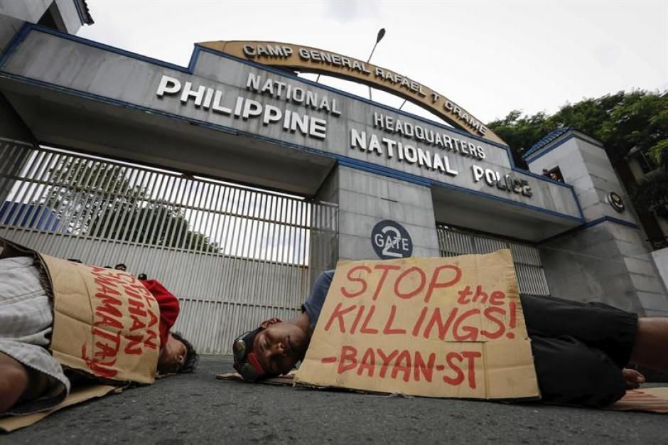 Manifestantes filipinos simulan ser víctimas de un asesinato extrajudicial frente a la sede de policía. (Foto: EFE)