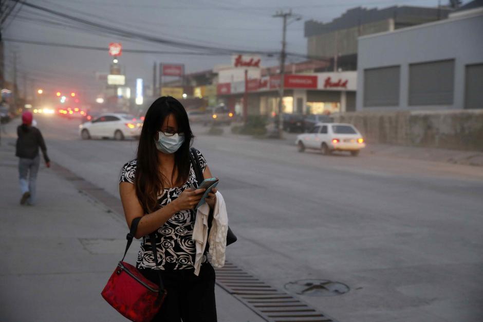 Las personas cubren sus rostros debido a la ceniza que cae en la ciudad de San José. (Foto: EFE)