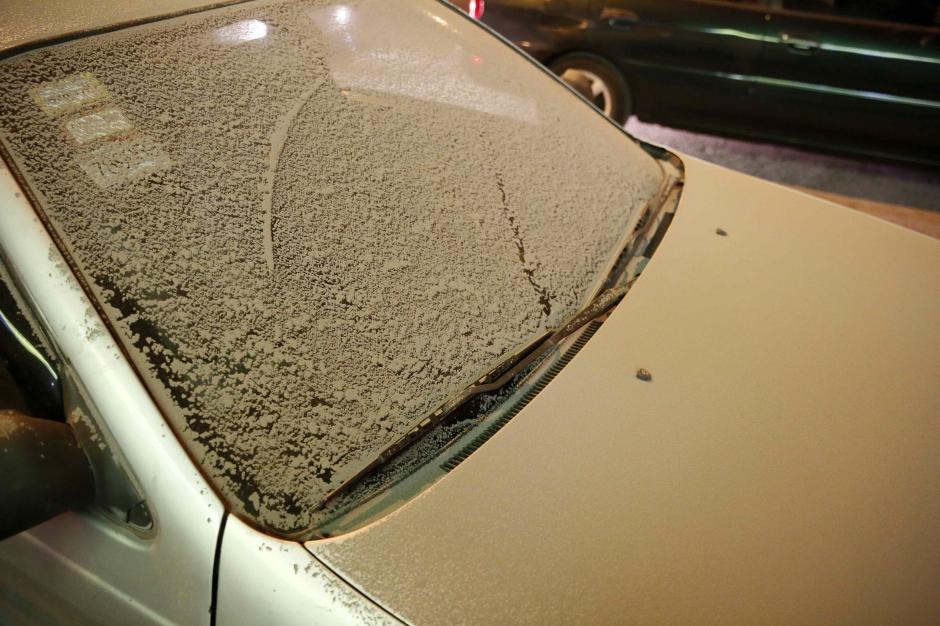 Las capas de ceniza cubren calles y autos en la ciudad.  (Foto: EFE)