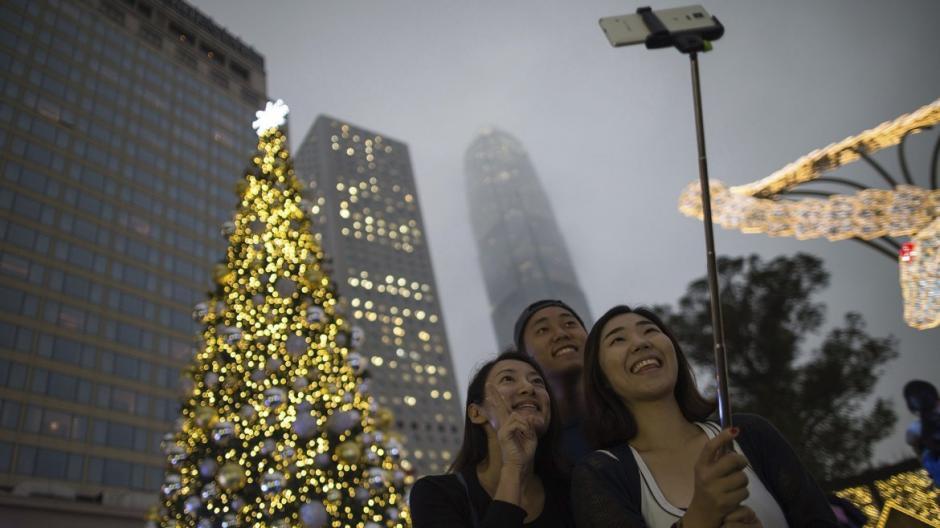 Amigos se toman un selfie junto a un árbol de Navidad, en Hong Kong, China. (Foto: EFE)