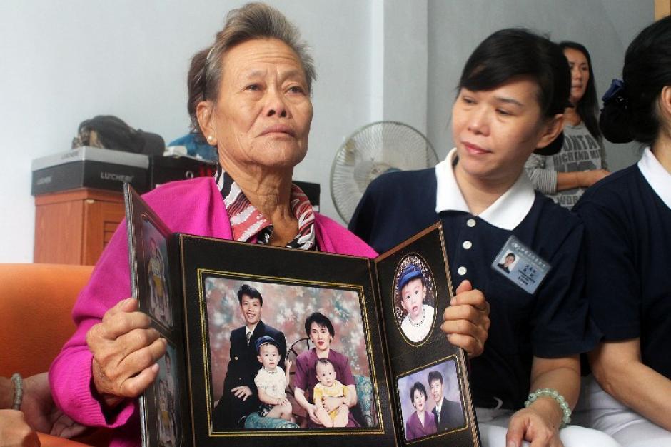Una mujer indonesia muestra el retrato de su hijo y su familia, quienes iban dentro del avión