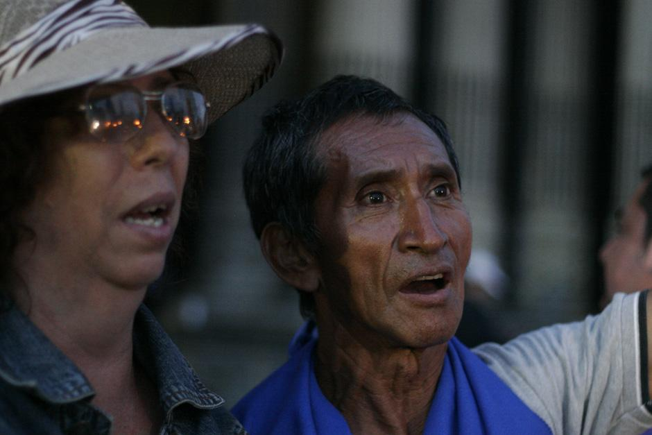 Dos ciudadanos entonan el Himno Nacional al caer la noche en el Centro Histórico de la zona 1.(Foto: José Dávila/Soy502)