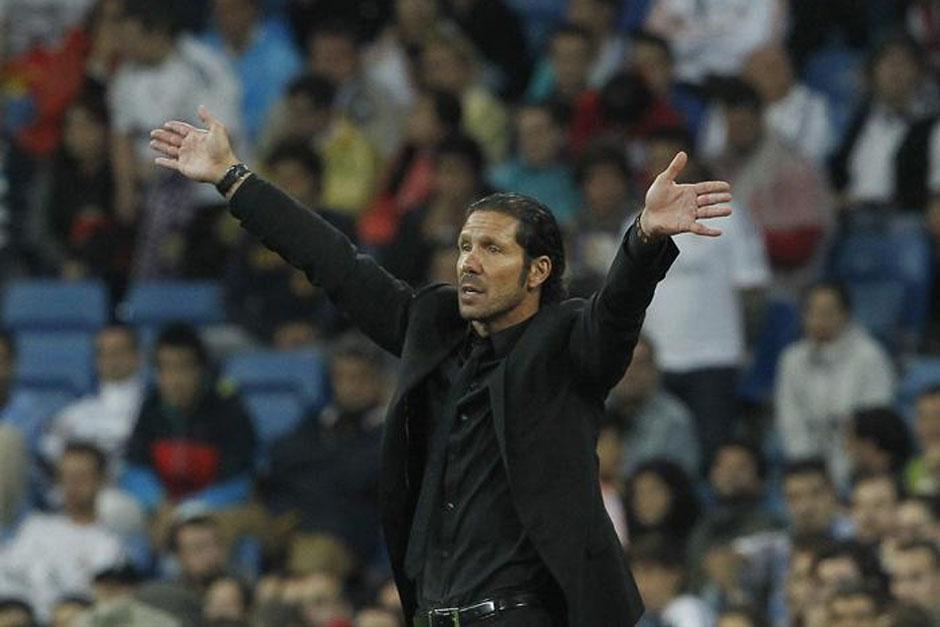 Diego Simeone extiende los brazos desde el banquillo del Atlético.