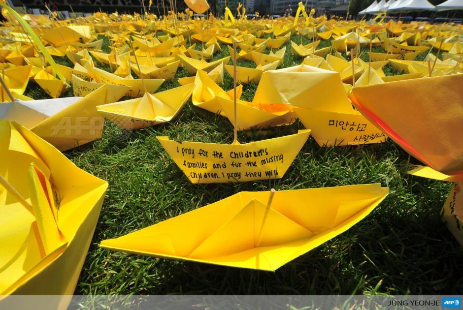 """Mensajes en barcos de papel son parte de un homenaje para las víctimas del ferry """"Sewol"""" en Seúl, que se hundió en abril con cientos de estudiantes de secundaria. El gobierno coreano ha informado que equipos de rescate terminarán la búsqueda de cuerpos en Corea del Sur este fin de semana. (Foto: AFP)"""