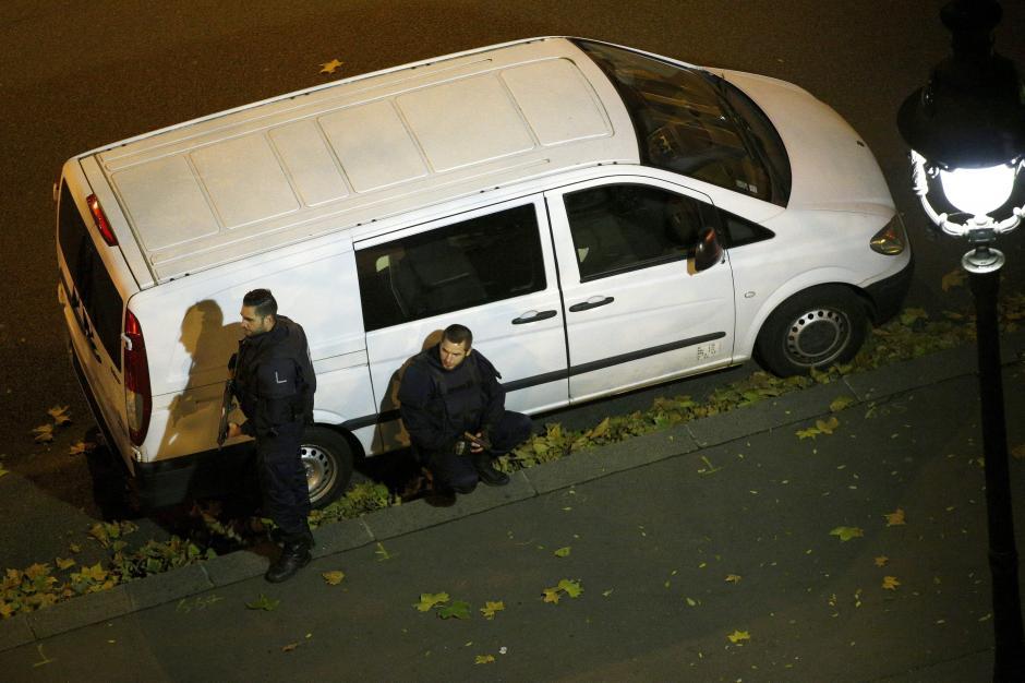 Agentes de la policía francesa se resguardan en las afueras del teatro Bataclán, donde terroristas retienen a una cantidad no determinada de rehenes. (Foto: EFE)