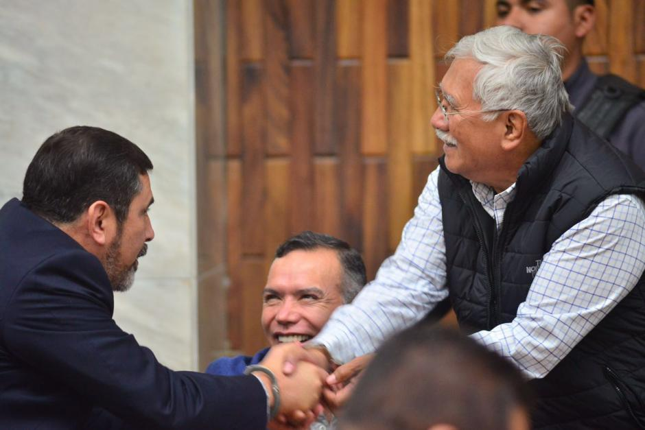 Edin Barrientos, miembro de la junta directiva de Banrural, saluda al exministro Ulises Anzueto. (Foto: Jesús Alfonso/Soy502)