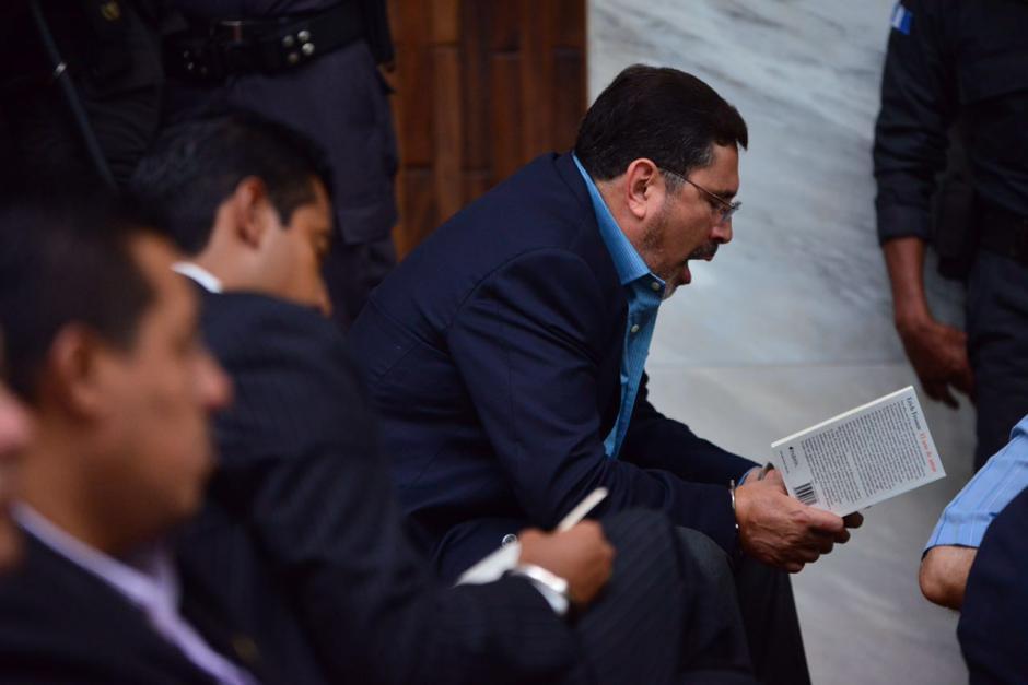 """El exministro de Defensa, Ulises Anzueto lee el libro """"El Arte de Amar"""" de Erich Fromm, mientras inicia la audiencia. (Foto: Jesús Alfonso/Soy502)"""