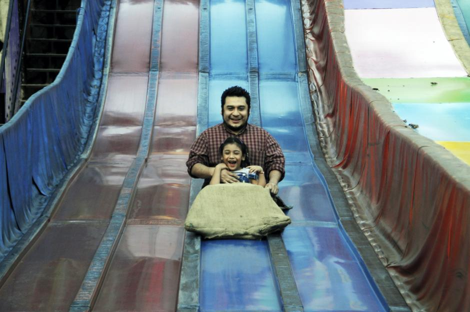 Un padre se resbala junto a su hija en los toboganes gigantes que hay dentro del Zoo. Este fue un día para celebrar y compartir tiempo juntos.