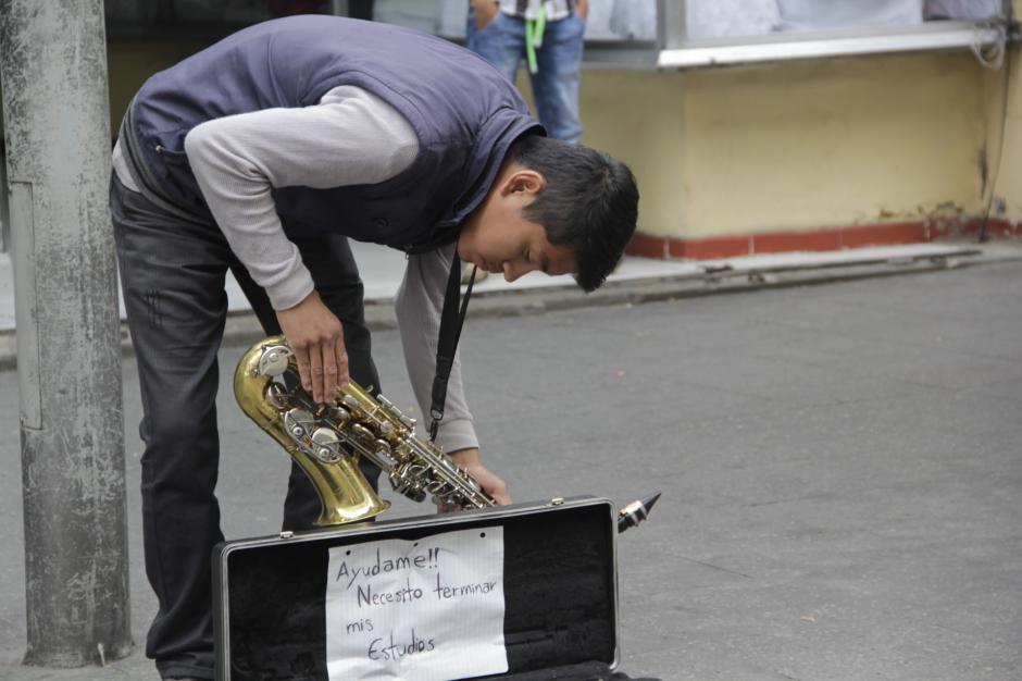 El joven músico abre el estuche de su saxofón con la esperanza que los transeúntes de la Sexta Avenida lo apoyen con algunas monedas. (Foto: Fredy Hernández/Soy502)