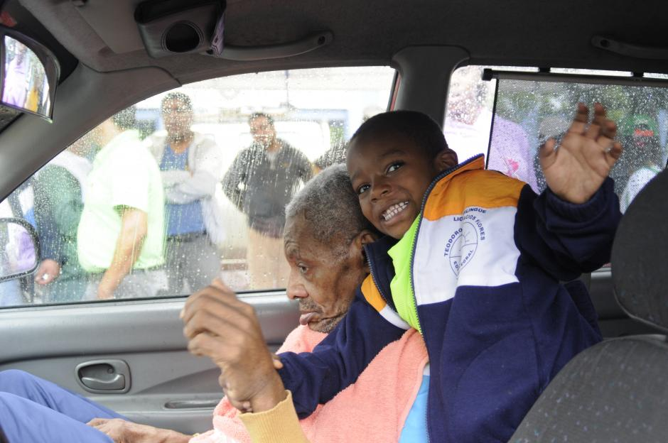 """Teodoro Palacios Flores permaneció en un vehículo mientras se disputaba la carrera """"Yo corro por un héroe""""; debido a la lluvia que azotó la capital guatemalteca este domingo. Cuando disminuyó el agua """"Teddy"""" compartió un rato con los participantes de la carrera. En la foto aparece con su nieto Ángel David, quien lo abrazaba y acompañaba.(Foto: Pedro Pablo Mijangos/Soy502)"""