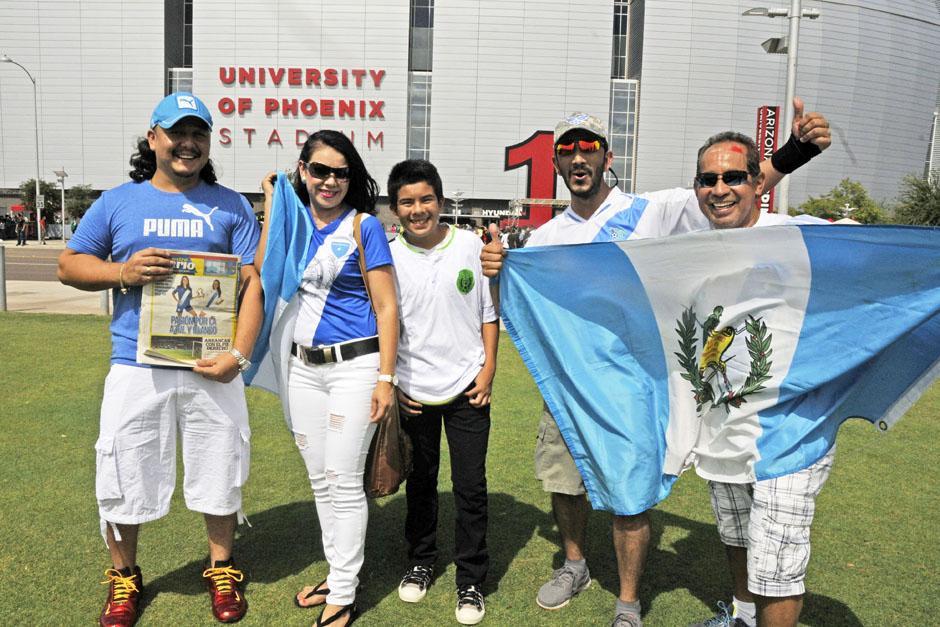 Guatemaltecos posando con una edición impresa de Nuestro Diario afuera del estadio de la Universidad de Phoenix