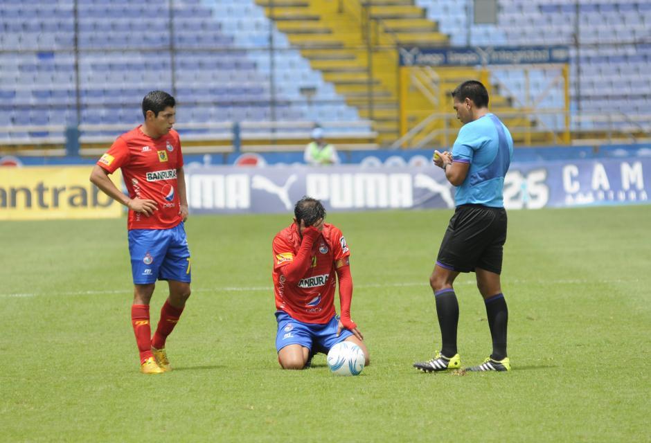 """El """"Pescado"""" Ruiz se duele después de una dura entrada, se toma la cara mientras el árbitro Walter López anota a Wilson Lalín con tarjeta amarilla. (Foto: Pedro Pablo Mijangos/Soy502)"""