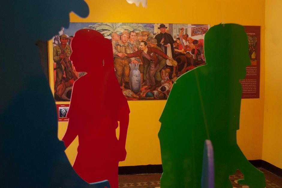 Una réplica fotográfica de la Gloriosa Victoria de Diego Rivera es exhibida en otra sala; en la misma se denuncia la invasión de Guatemala por fuerzas militares de Estados Unidos para derrocar al Gobierno de Jacobo Arbenz y defender los intereses de la poderosa compañía bananera United Fruit Company, en 1954. (Foto: Jesús Alfonso/Soy502)