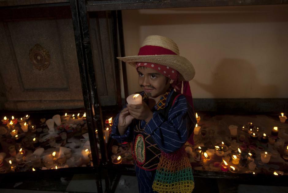 Un niño, llamado Osman Najarro, es fotografiado por un familiar mientras ofrece su veladora a la Virgen, en un día especial para él. (Foto: Jesús Alfonso/Soy502)