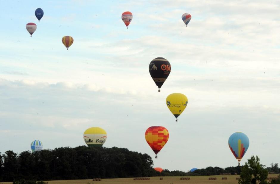 La gente mira a los globos que vuelan como parte de los 40a Campeonatos franceses Air-globo, el 19 de agosto de 2014, en Sable-sur-Sarthe, al oeste de Francia, en el que 47 globos competirán hasta el 23 de agosto (Foto: AFP/ JEAN-FRANCOIS MONIER)