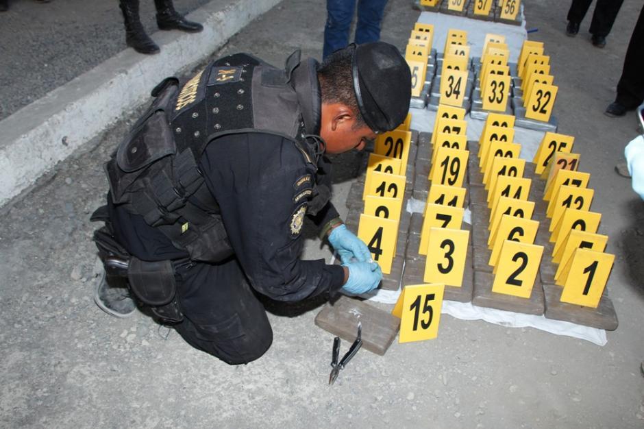 Un agente antinarcótico muestra los paquetes de cocaína y heroína localizados en el interior de los contenedores. Foto:PNC