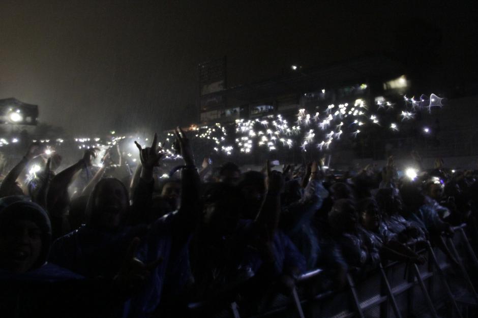 Las luces de los celulares iluminaban la oscuridad antes que la banda saliera al escenario. (Foto: Fredy Hernández/Soy502)