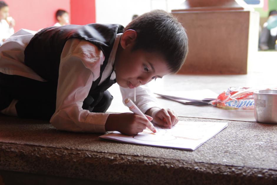 En Los Patojos no hay momentos para dejar de crear y dibujar sueños. José Manuel pinta en su libro de dibujos tras terminar su almuerzo.(Foto: Fredy Hernández/Soy502)
