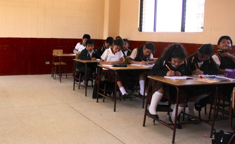 Al fondo del aula del cuarto grado de primaria, el lugar del pequeño Fernando Emanuel lo llena el recuerdo y la amistad que sembró con sus compañeros.(Foto: Fredy Hernández/Soy502)