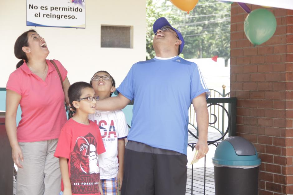 Sorprendidos, los cuatro integrantes de la familia ven caer los globos que eran sostenidos en la manta que los identificaba como el visitante 70 millones. (Foto: Fredy Hernández/Soy502)