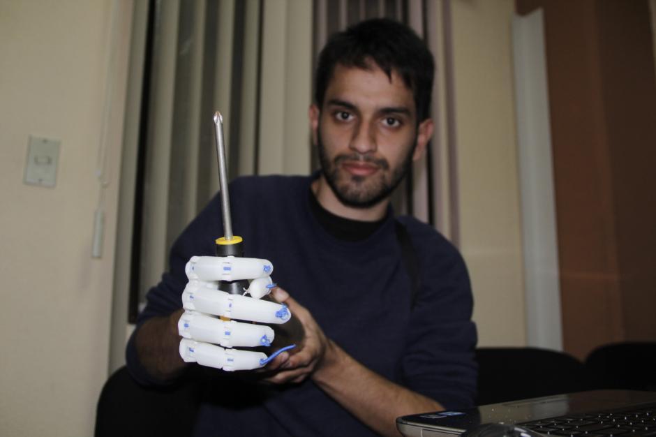 Mario muestra el beneficio de tener una prótesis para los pacientes. Para muchas personas es muy fácil sostener cualquier objeto, pero cuando no tienes una extremidad, la tarea es más difícil.(Foto: Fredy Hernández/Soy502)