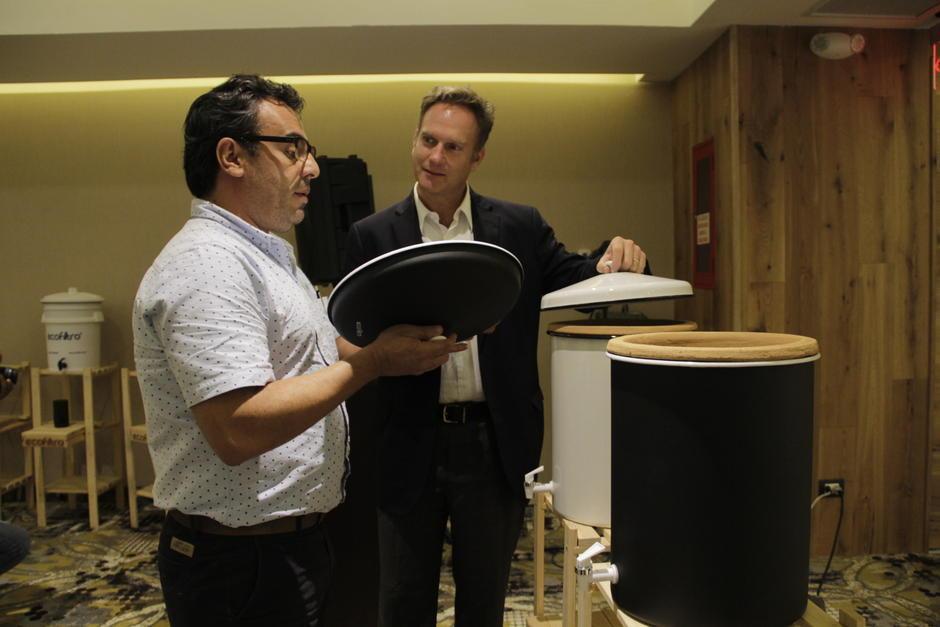 Philip Wilson, izquierda, muestra los nuevos modelos de Ecofiltro elaborados con peltre. (Foto: Fredy Hernández/Soy502)