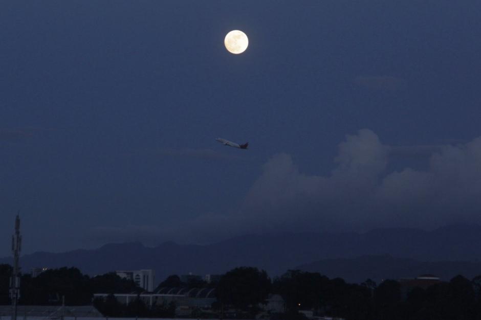 Un avión pasa debajo de la luna al final de la tarde. (Foto: Fredy Hernández/Soy502)