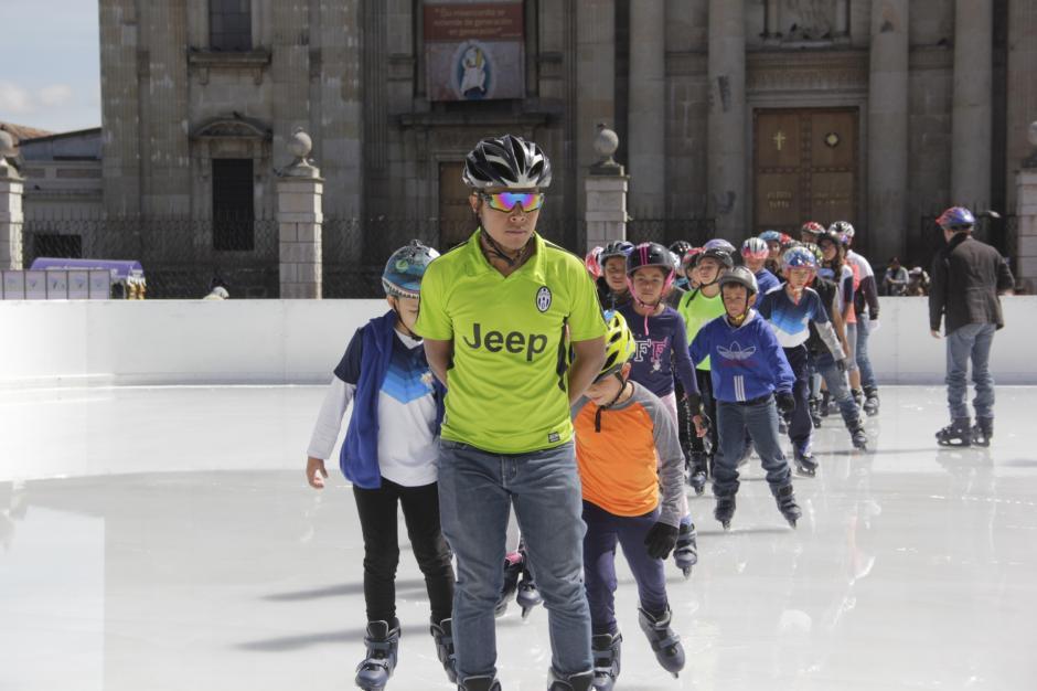 Un instructor guía a los niños sobre la pista congelada. (Foto: Fredy Hernández/Soy502)