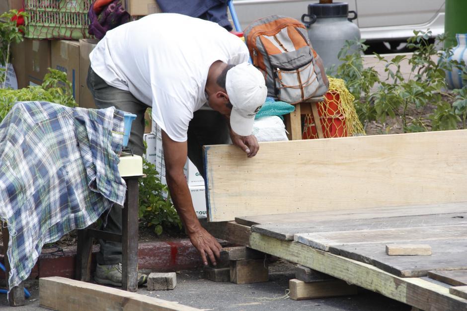 Un vendedor clava varias piezas de madera que forman el piso de una de las tiendas de feria.(Foto: Fredy Hernández/Soy502)