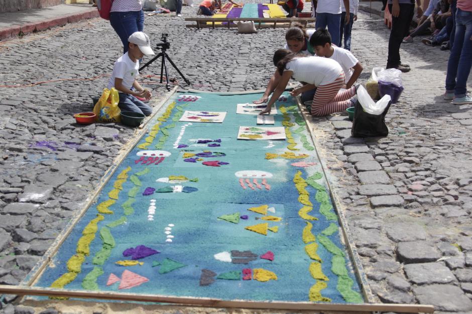 Un grupo de niños elabora una alfombra con diseños de especies marinas. (Foto: Fredy Hernández/Soy502)